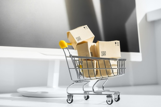 Conceito de compras online. carrinho de compras pequeno com muitas caixas de papel