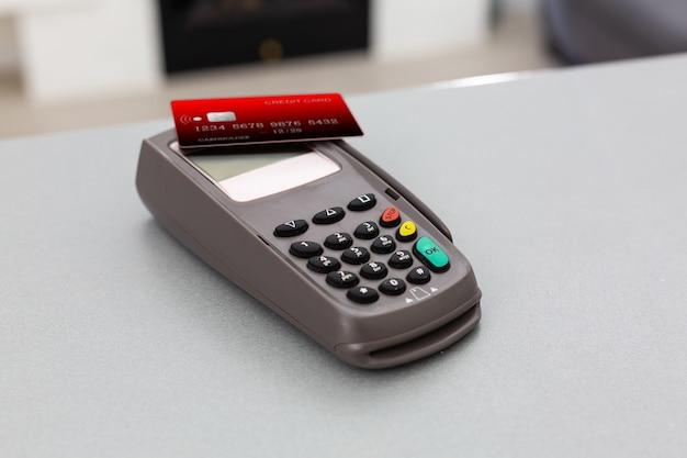 Conceito de compras online. close de uma caixa registradora ao lado de um carrinho em um fundo cinza, vista superior, espaço de cópia