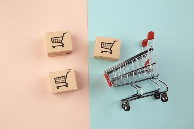 Conceito de compras online e comércio eletrônico via internet: caixas ao lado de um carrinho de compras ou carrinho de metal.