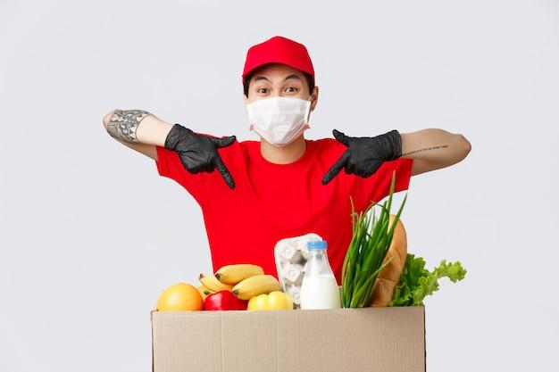 Conceito de compras online, entrega de comida e coronavírus. correio asiático sorridente, apontando o dedo para o pacote com mantimentos frescos, entrega as mercadorias na casa do cliente durante a quarentena, pedido online do cliente.