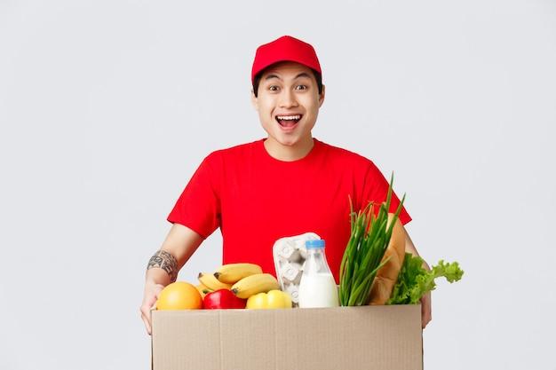 Conceito de compras online, entrega de comida e lojas de internet. correio asiático sorridente amigável com boné vermelho e t-shirt, segurando o pacote com mantimentos, produtos frescos para o pedido do cliente.
