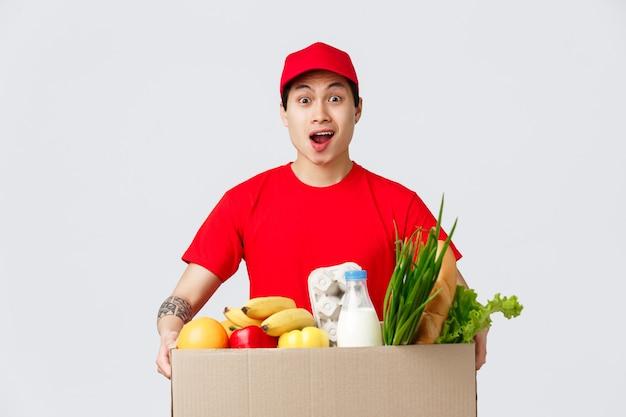 Conceito de compras online, entrega de comida e lojas de internet. entregador asiático chocado carregando uma caixa enorme de pedidos de clientes, segurando um pacote de produtos de mercearia, mensageiro surpreso