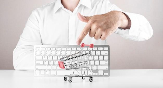Conceito de compras online. homem apontando no carrinho de compras vazio com o teclado no fundo