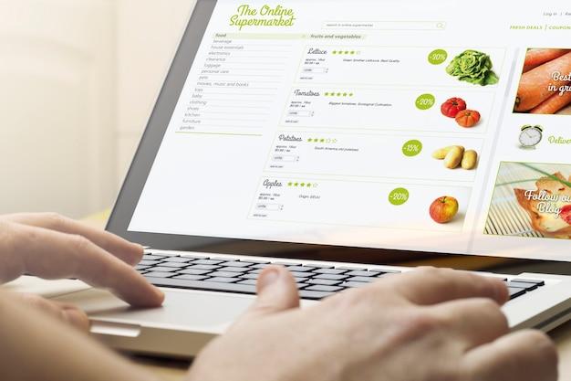 Conceito de compras online. homem usando um laptop com o site do supermercado na tela.
