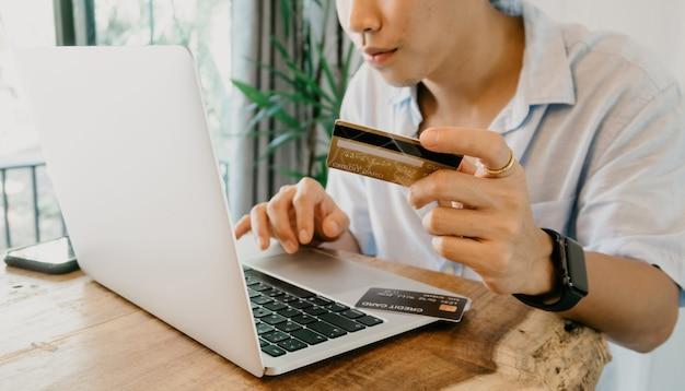 Conceito de compras online homens asiáticos estão usando cartões de crédito para inserir códigos para fazer compras usando um laptop.
