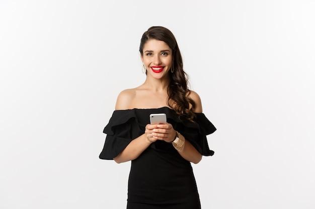Conceito de compras online. jovem de vestido preto, lendo mensagem de texto, usando telefone celular e sorrindo, em pé sobre um fundo branco.