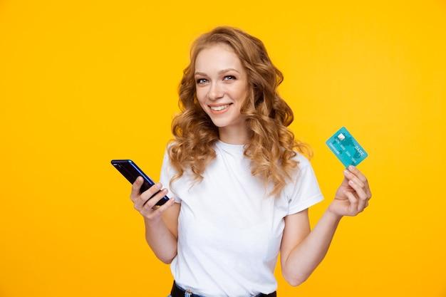 Conceito de compras online. jovem mulher bonita segurando o telefone e o cartão de crédito azul em pé no estúdio amarelo.