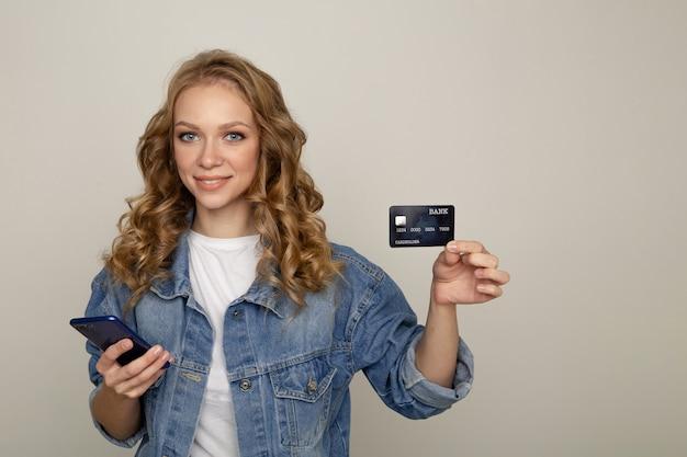 Conceito de compras online. jovem mulher bonita segurando o telefone e o cartão de crédito em pé no estúdio branco.