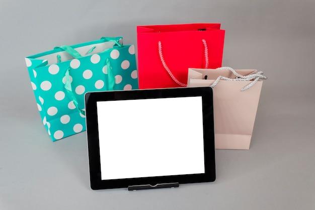 Conceito de compras online. maquete de tablet de close-up com tela branca com sacos de presente brilhante em fundo cinza.