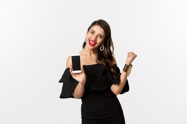 Conceito de compras online. mulher bonita satisfeita mostrando a tela do smartphone, fazendo o punho bombear para se alegrar, ganhando na internet, em pé sobre um fundo branco.