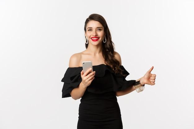 Conceito de compras online. mulher de vestido preto na moda, maquiagem, mostrando o polegar para cima e usando o aplicativo do telefone móvel, fundo branco.