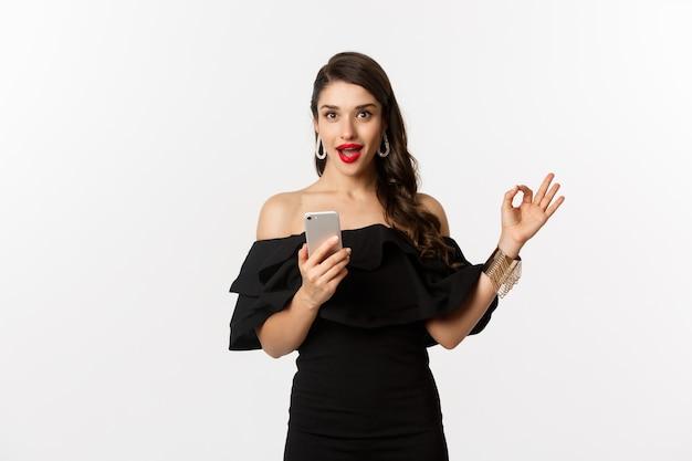 Conceito de compras online. mulher de vestido preto na moda, maquiagem, mostrando o sinal de aprovação e usando o aplicativo do telefone móvel, fundo branco.