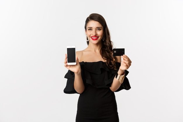 Conceito de compras online. mulher morena elegante de vestido preto, mostrando a tela do celular e o cartão de crédito, sorrindo satisfeito, em pé sobre um fundo branco.