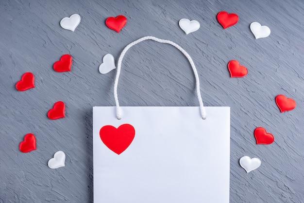 Conceito de compras online. saco de compras branco brilhante e corações brancos e vermelhos em cinza moderno