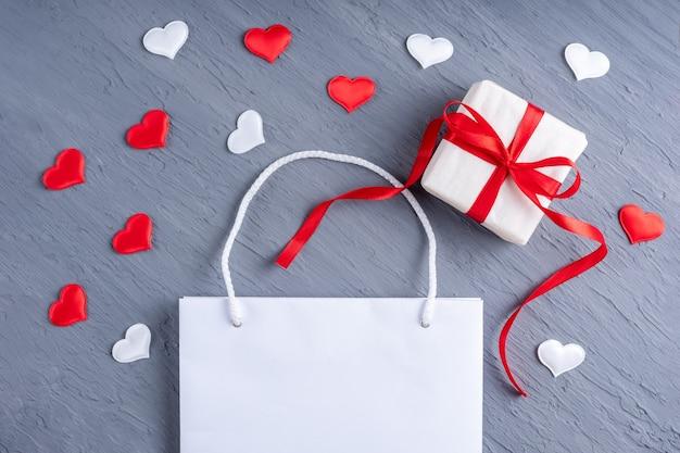 Conceito de compras online. saco de compras branco brilhante e presente com laços de fita vermelha
