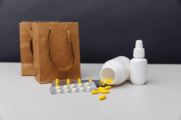 Conceito de compras online. sacos com medicamentos controlados manipulados enviados de uma farmácia por correspondência em um fundo cinza.
