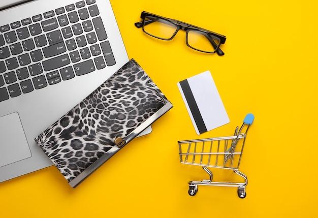 Conceito de compras online. supermercado online. carrinho de compras, cartão de banco, carteira, laptop em um amarelo. camada plana, vista superior