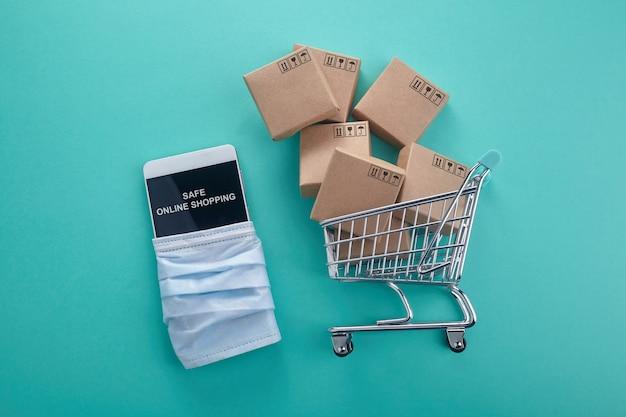Conceito de compras online. telefone inteligente com carrinho de compras no fundo da casa da moeda. quarentena em casa. vista do topo.