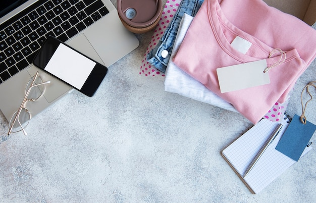 Conceito de compras online. um laptop e um conjunto de roupas femininas em uma caixa de papelão. entrega de roupas.