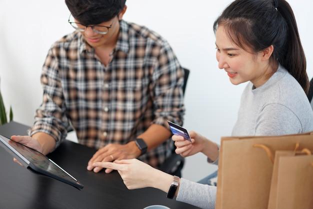 Conceito de compras online um lindo casal adicionando informações de cartão de crédito para usar em transações financeiras online.