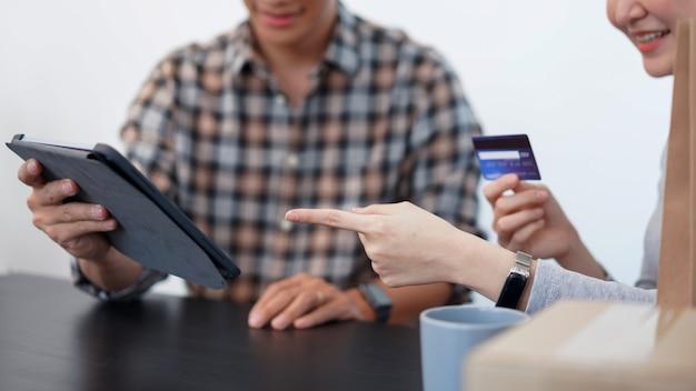 Conceito de compras online: um lindo casal adicionando informações de cartão de crédito