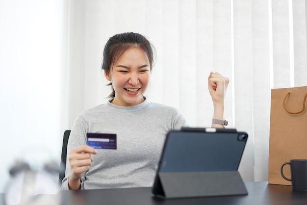 Conceito de compras online: uma compradora feliz por receber um desconto