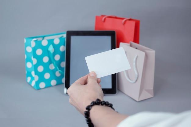 Conceito de compras online. uma garota tem um cartão de crédito nas mãos, contra a parede de uma maquete de tablet com uma tela branca e lindos sacos de presente.
