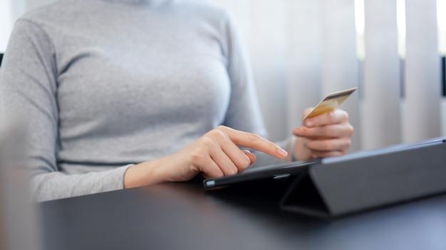 Conceito de compras online: uma mulher do meio adulto usando seu cartão de crédito para fazer uma transação financeira em seu ipad.