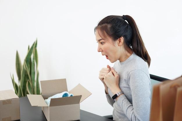 Conceito de compras online: uma mulher sorridente desembalando um pacote que chega para verificar os produtos que comprou depois de esperar com esforço.