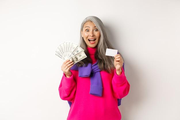 Conceito de compras. vovó asiática espantada mostrando cartão de crédito de plástico e dólares de dinheiro, quer comprar algo, em pé sobre um fundo branco.