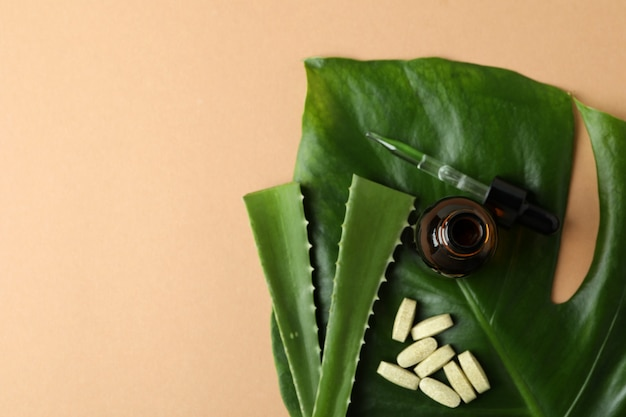 Conceito de comprimidos de ervas e cosméticos com babosa em fundo bege