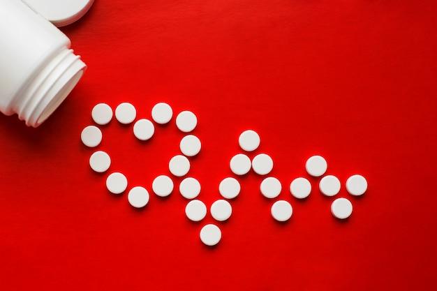 Conceito de comprimidos para doenças cardíacas e cardiovasculares. comprimidos brancos dormem o suficiente em um frasco branco e formam um cardiograma e um símbolo do coração em um fundo vermelho. copie o espaço. fundo isolado