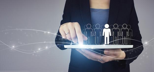 Conceito de comunidade, unidade, pessoas e apoio. tablet branco na mão da mulher de negócios com holograma digital humano, sinal de ícone de líder em fundo cinza. recrutamento emprego headhunting concept.