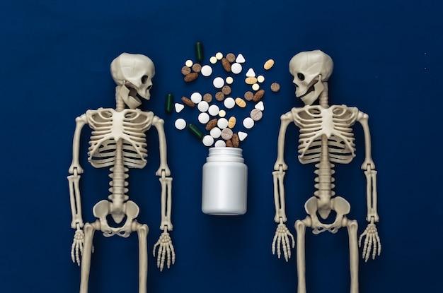 Conceito de conceito de medicamento ou narcótico. dois esqueletos e frasco de comprimidos em azul clássico
