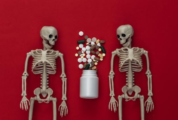 Conceito de conceito de medicamento ou narcótico. dois esqueletos e frasco de comprimidos no vermelho