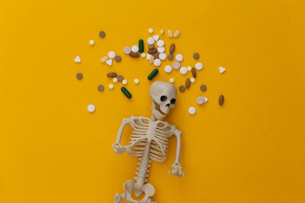 Conceito de conceito de medicamento ou narcótico. esqueleto e comprimidos em amarelo