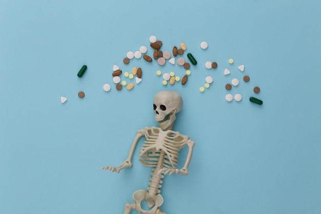 Conceito de conceito de medicamento ou narcótico. esqueleto e comprimidos em azul