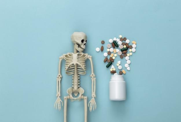 Conceito de conceito de medicamento ou narcótico. esqueleto e frasco de comprimidos em azul