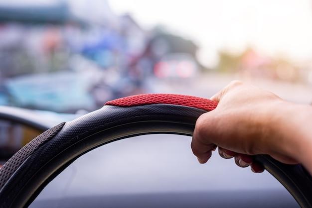 Conceito de condução, mão dirigindo um carro na estrada fundo desfocado
