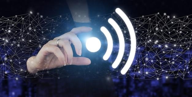 Conceito de conexão de rede de negócios e wi-fi na cidade. mão segure o holograma digital wi fi cadastre-se no fundo desfocado escuro da cidade.