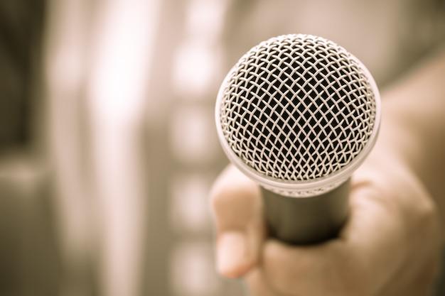 Conceito de conferência de seminário: mãos de empresários segurando microfones para falar ou falar na sala de seminário, falando para palestra para a universidade de público, fundo do salão de convenções de luz de evento.