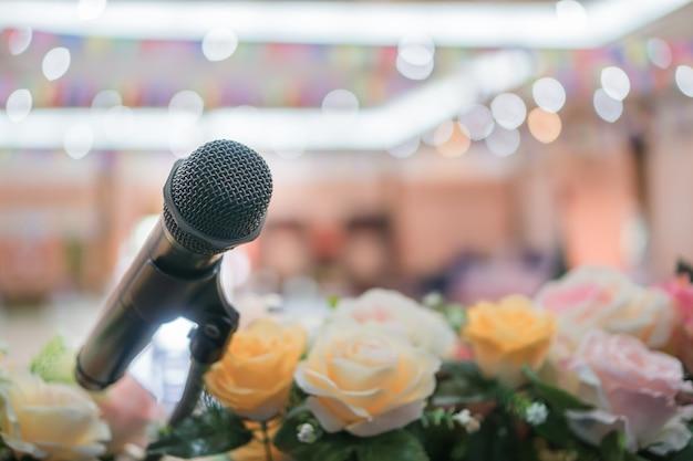 Conceito de conferência do seminário: microfones de close-up no desfoque abstrato da fala na sala de reuniões, flores na frente falando borrão luz bokeh no salão de convenções de eventos no fundo do hotel