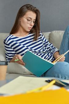 Conceito de conhecimento e educação. menina caucasiana séria, de cabelos escuros, usando óculos grandes e roupas listradas, gosta de aprender em casa, senta-se no sofá e se prepara para um seminário