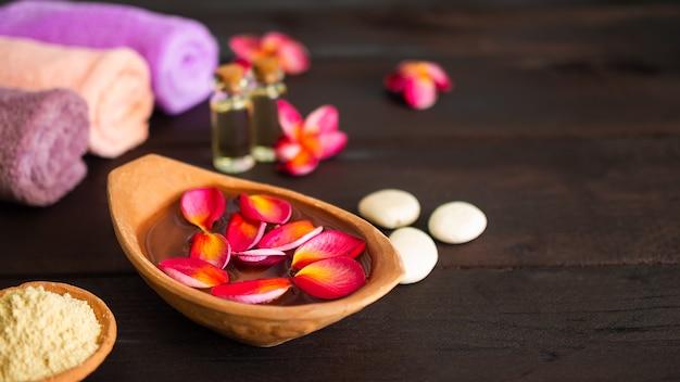Conceito de conjunto de spa de aromaterapia. pétalas de plumeria vermelha flutuando em uma panela de barro