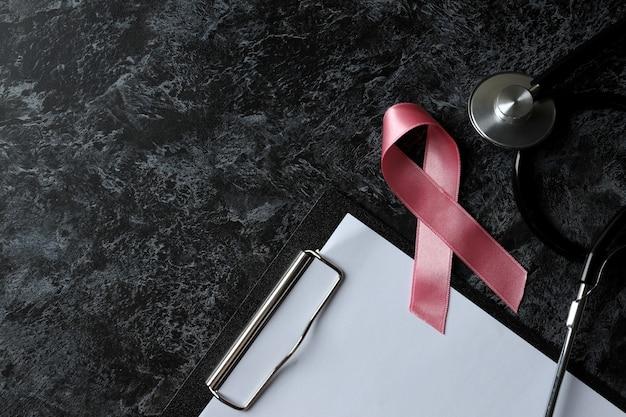 Conceito de conscientização do câncer de mama em mesa preta esfumada
