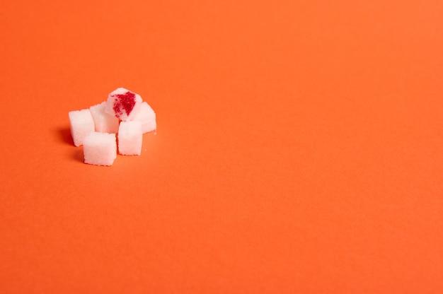 Conceito de conscientização do dia mundial da diabetes, 14 de novembro. cubos de açúcar branco puro refinado com gota de sangue, isolados sobre fundo colorido laranja com espaço de cópia para publicidade médica