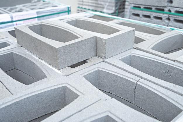 Conceito de construção, blocos de tijolos em paletes no armazém.