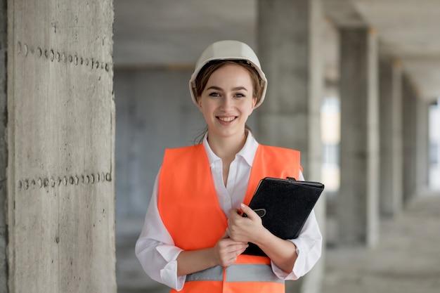Conceito de construção de engenheiro ou arquiteto trabalhando no canteiro de obras. uma mulher com um tablet em uma construção. escritório de arquitetura.