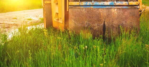 Conceito de construção de uma área residencial com maquinário pesado, rolo-compactador em campo verde