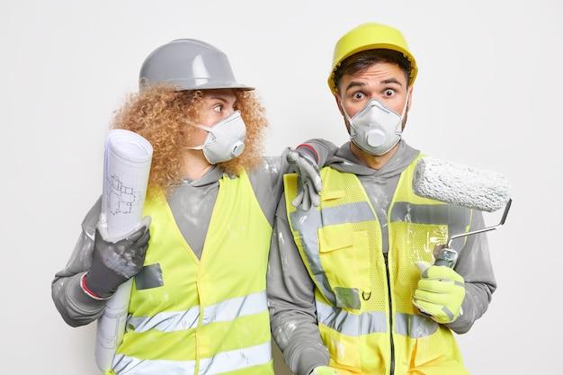 Conceito de construção e engenharia de reparação. equipe de trabalhadores de manutenção chocados, vestidos com roupas de trabalho, segurando a planta do papel e pintando com rolo de pintura na parede interior do projeto